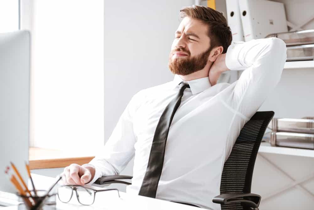 uomo in ufficio con postura scorretta